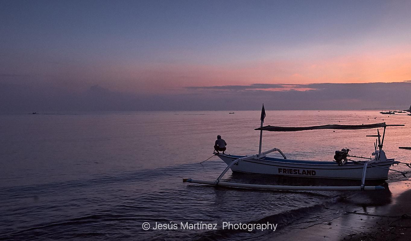Pescador preparando su barca al amanecer